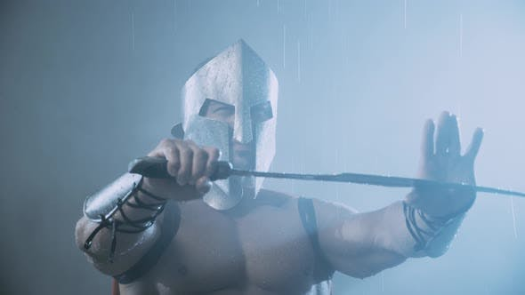 Thumbnail for Muscular Spartan Holding Blade on Thumb Under Rain.