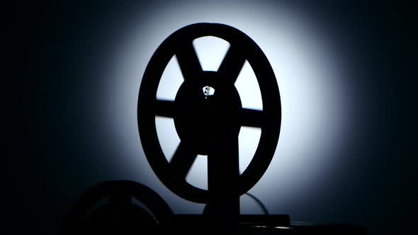 Bobbin Movie Projector Reels Film. Silhouette in a Dark Studio