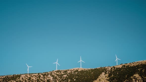 Thumbnail for Time Lapse of Wind Mill Turbines on Top of Mountain Range Against Bright Blue Sky