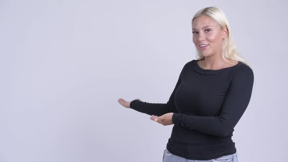 Thumbnail for Young Happy Blonde Woman Showing Something