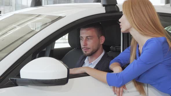 Thumbnail for Handsome Man Talking To His Wife While Choosing New Car at Dealership Salon