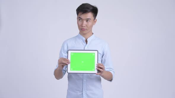 Young Happy Asian Businessman Thinking While Showing Digital Tablet