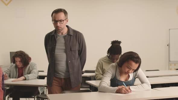 Teacher Taking Away Cheat Sheet from Student