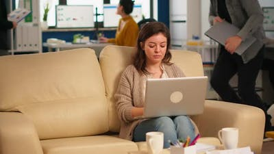 Young Woman Entrepreneur Sitting on Couch Looking at Camera