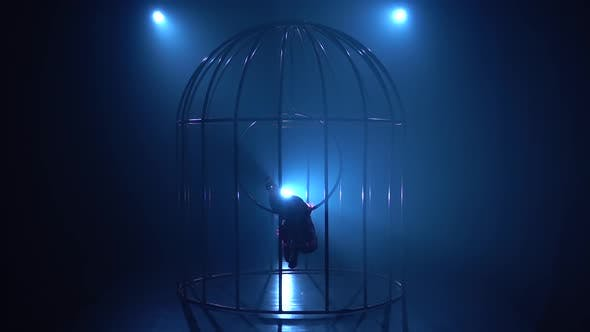 Thumbnail for Aerial Acrobatics on a Rotating Hoop in Cage in a Dark Room. Blue Smoke Background. Silhouette