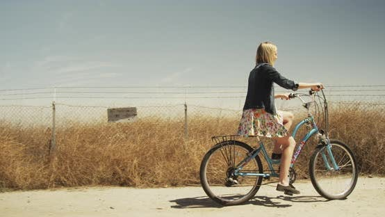 Thumbnail for Beautiful young woman riding bike by the countryside