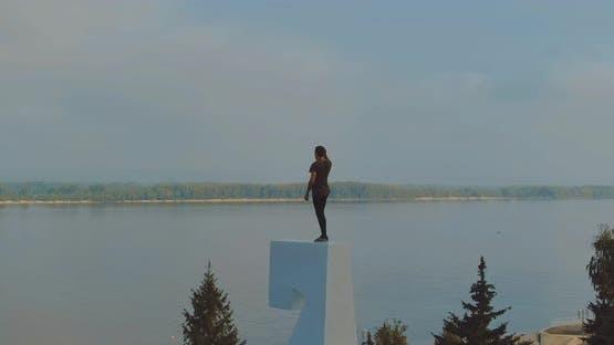 Mann steht auf einem sehr hohen Sockel und bietet einen schönen Panoramablick auf den Fluss