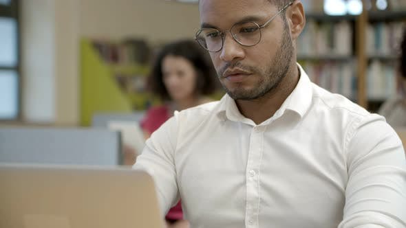Thumbnail for Front View of Focused Young Man Using Laptop at Library