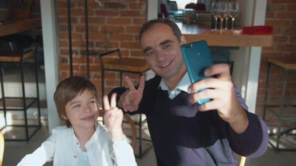 Father and Son Take Selfie on the Phone in Cafe