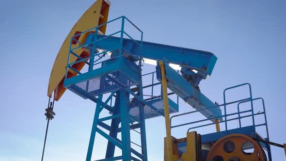 Thumbnail for Industrial Equipment Is Pumping Petroleum and Natural Gas From Ground, Tilt Up View Against Blue Sky