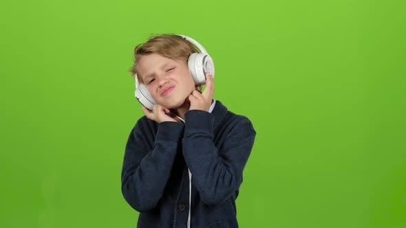 Thumbnail for Child in the Headphones Is Listening To Music. Green Screen