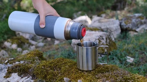 Warm Tea Poring Out From a Thermos in Cup