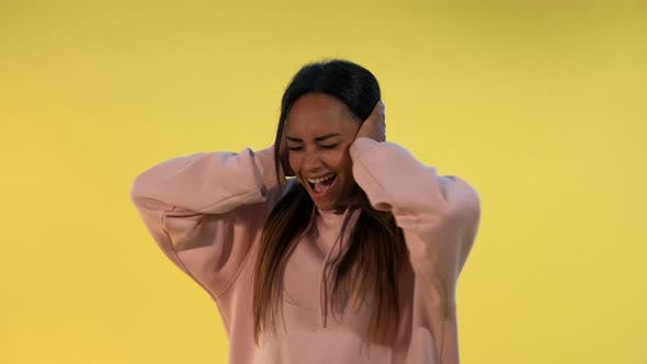 Thumbnail for Desperate African Woman Screaming and Covering Ears on Yellow Background