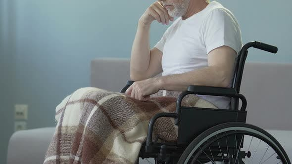 Thumbnail for Injured man sitting in wheelchair, starting to push it hands striving to recover
