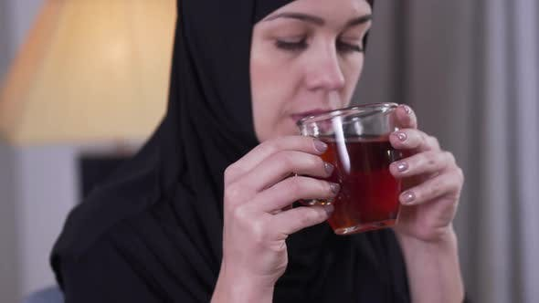 Thumbnail for Camera Following Cup of Tea in Female Hands. Charming Serious Muslim Woman in Traditional Hijab