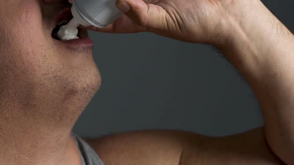 Cover Image for Closeup of Overweight Man Stuffing with Whipped Cream, Overeating Disorder