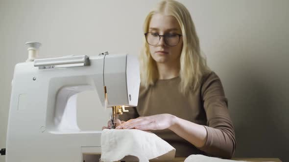 A Young Woman Sews Clothes Sitting in a Light Workshop at a Table with a Sewing Machine