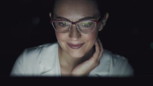 Reflection of the Monitor Screen with Glasses. Young Woman Working Late in the Office
