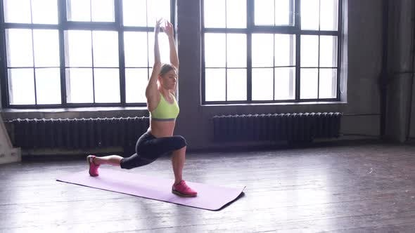 A young Blonde Woman Doing a Stretching Exercise with her Hands sitting On a sports