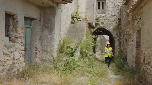 girl with yellow helmet and high visibility jacket walking through the alleys of a village