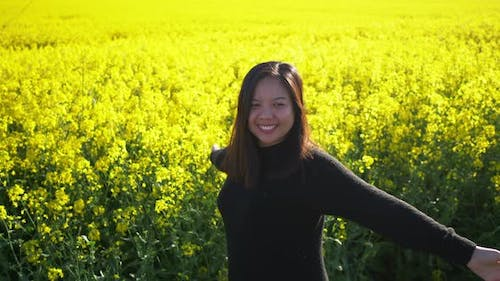 Asian woman standing, turning around and raising her hands in yellow field