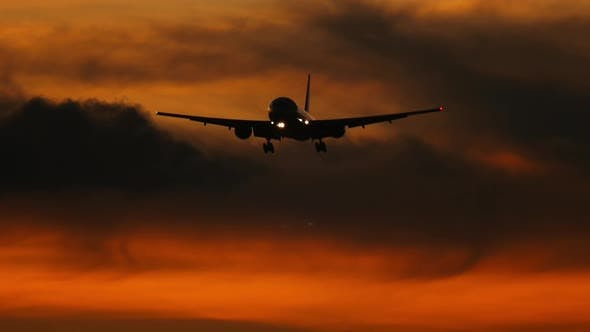 Airplane silhouette in the sunset sky
