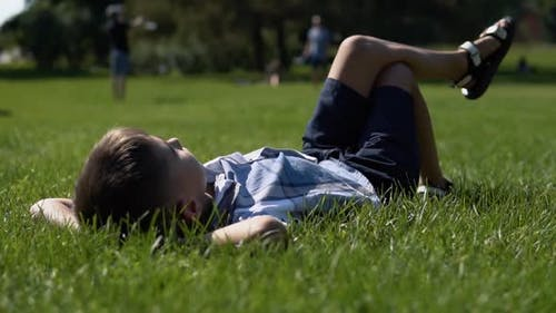 An Attractive Boy Lies in a Park on the Grass Having a Good Mood During the Day in Sunny Weather