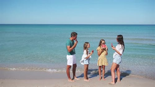 Happy Family Eating Watermelon on the Beach.