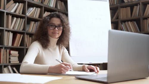 Smiling Hispanic School Math Teacher Looking at Camera in Classroom with Laptop