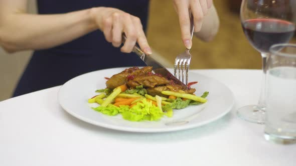 A Lady in an Evening Dress Eats Pork with Vegetables with a Fork and Knife.