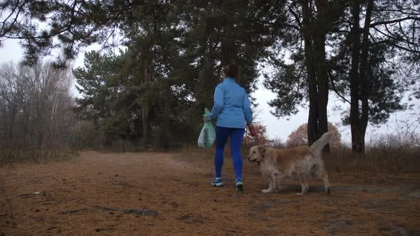 Thumbnail for Eco Friendly Woman with Pet Doing Plogging in Wood