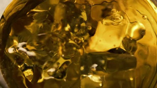 Macro shot of falling ice cube into glass with whiskey.