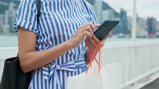 Thumbnail for Woman use of smart phone with holding shopping bag