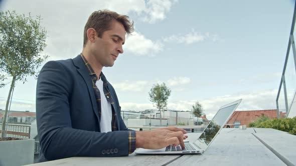 Thumbnail for Guy Using Laptop Outside