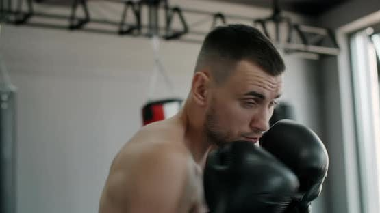 Kickboxer in Boxing Gloves Does Shadow Boxing and Trains at Boxing Club Fighter Man is Fighting with