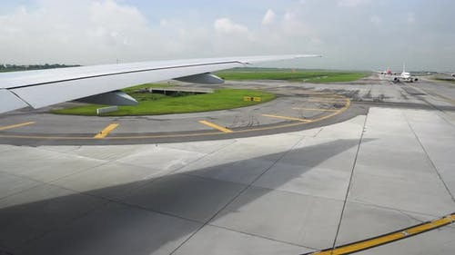 The Runway Under Wing of Aircraft. Airplane Moving on the Runway in Terminal of Departure in the
