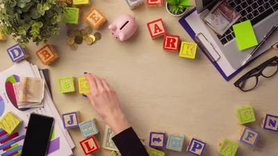 Woman Hand Arranging Wooden Cubes with Word ECONOMY