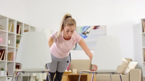 Cover Image for Sporty Woman Doing Push Ups on Two Chairs at Home