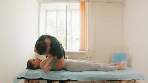 Osteopath Treatment - the Doctor Pushing on the Chest of Young Woman with Her Arms Crossed
