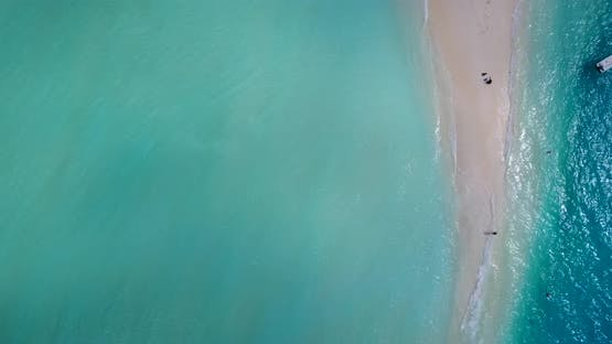 Wide fly over travel shot of a sandy white paradise beach and turquoise sea background in high resol