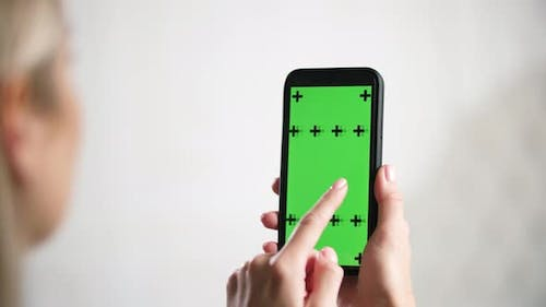 Girl Holds in Hands Iphone and Swipes Slides Green Mockup Chromakey Ads Screen