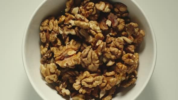 Walnuts Falling Into A White Bowl