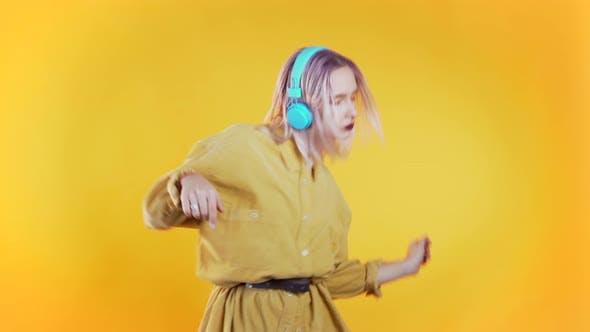 Thumbnail for Schöne Frau mit rosa Haare Tanzen mit Kopfhörern auf Gelb