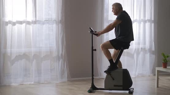 Training on Stationary Bicycle Middleaged Man Is Spinning Pedals Exercise for Health of