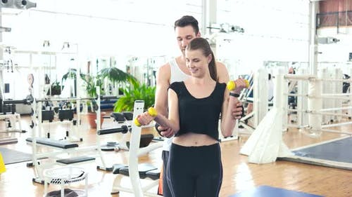 Male Trainer Assisting Woman Lifting Dumbbells.