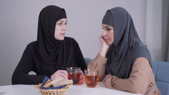 Cover Image for Modest Muslim Woman in Hijab Calming Down Her Modern-looking Female Friend. Young Lady Comforting