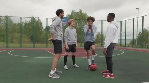 Cheerful Male Friends Flipping Coin before Streetball Game