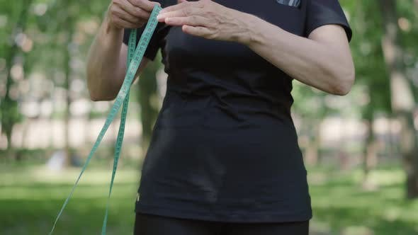 Thumbnail for Unrecognizable Mid-adult Sportswoman Measuring Waist with Tape. Confident Slim Caucasian Woman in