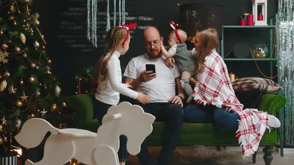 Thumbnail for Christmas Family Concept - Dad Sitting in His Phone - His Daughter Take Away the Phone and Baby