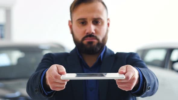 Thumbnail for Image for Graphic Implements. Businessman Holds a Tablet with HUD Futuristic Elements
